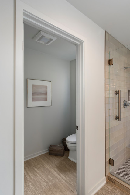 Example of a large transitional master beige tile and glass tile porcelain floor and gray floor bathroom design in Seattle with recessed-panel cabinets, gray cabinets, a one-piece toilet, gray walls, a vessel sink, engineered quartz countertops and a hinged shower door