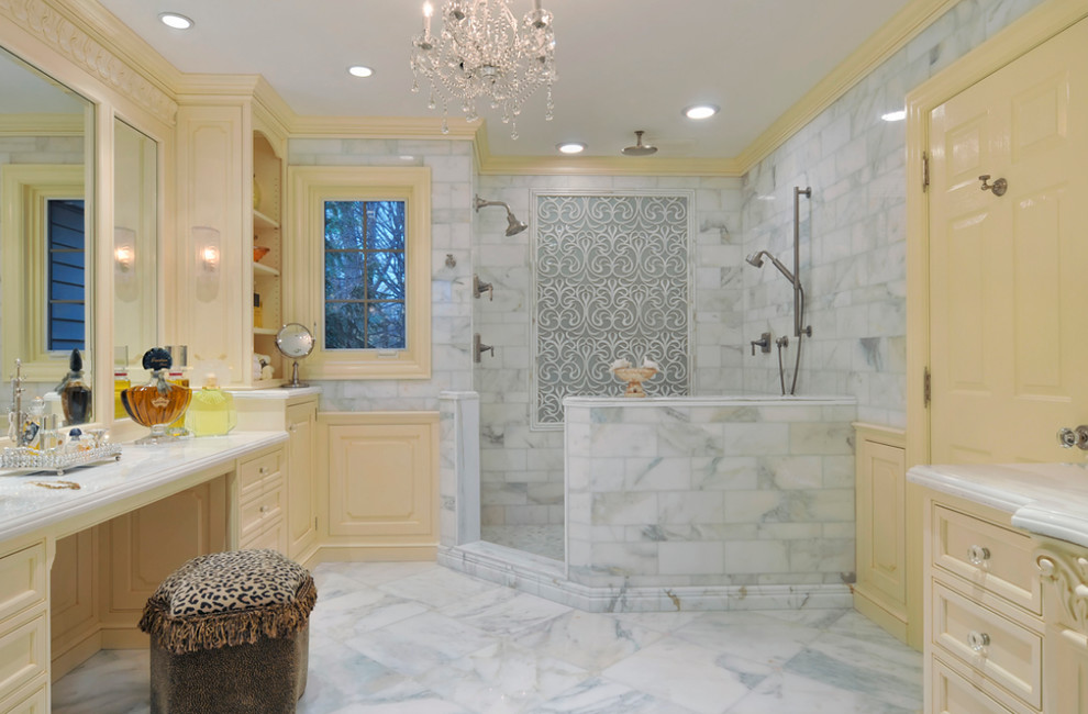 Example of a large classic master white tile and stone tile marble floor corner shower design in New York with yellow cabinets, yellow walls, a two-piece toilet, marble countertops and recessed-panel cabinets