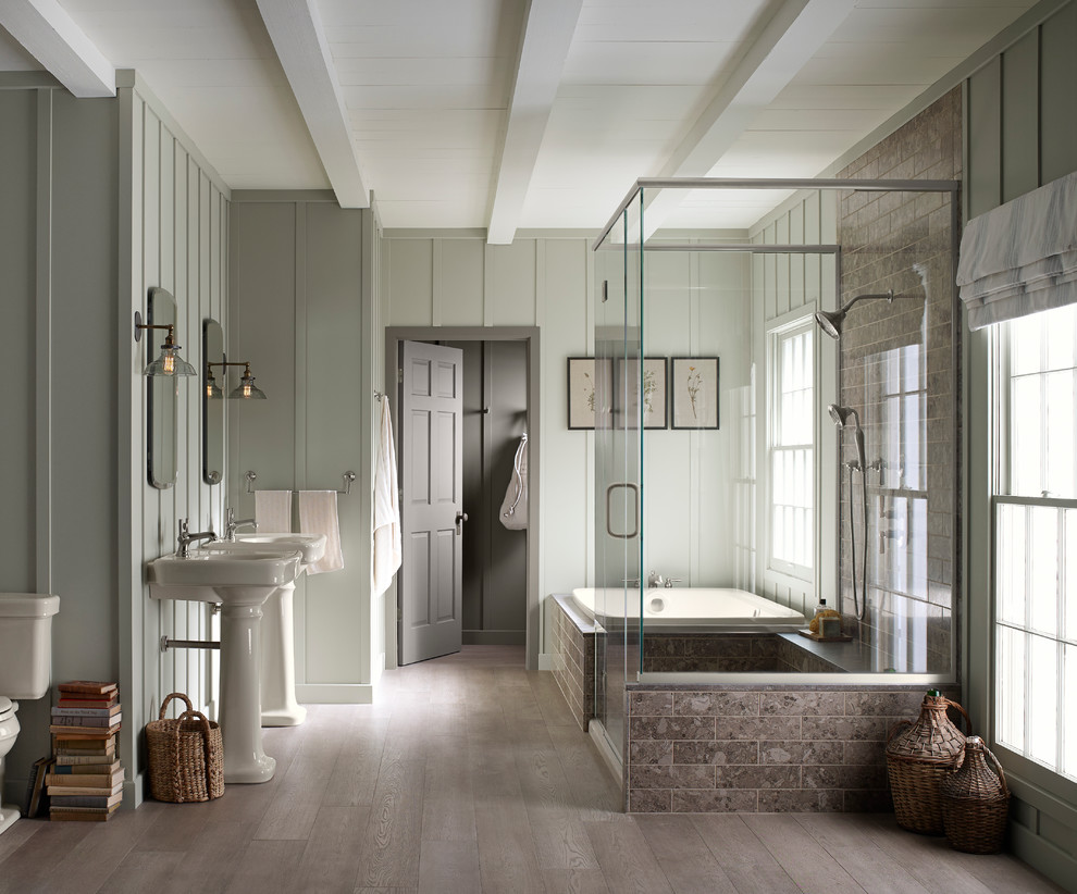 Example of a large farmhouse master light wood floor drop-in bathtub design in Milwaukee with a pedestal sink, a two-piece toilet and green walls