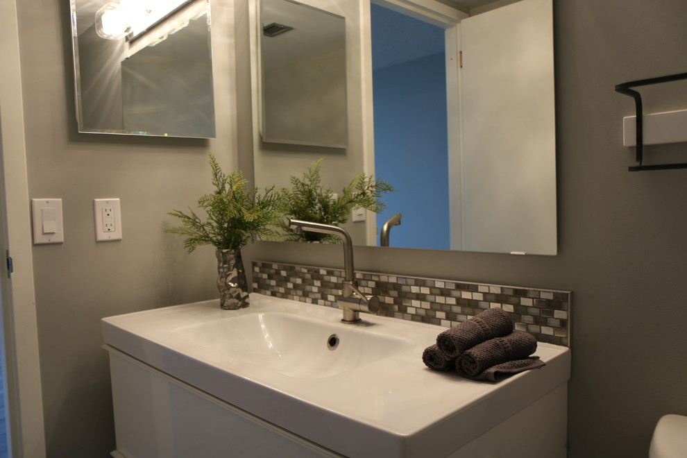 Inspiration for a small contemporary 3/4 gray tile and glass tile mosaic tile floor corner shower remodel in Calgary with flat-panel cabinets, white cabinets, a two-piece toilet, gray walls, an undermount sink and quartz countertops