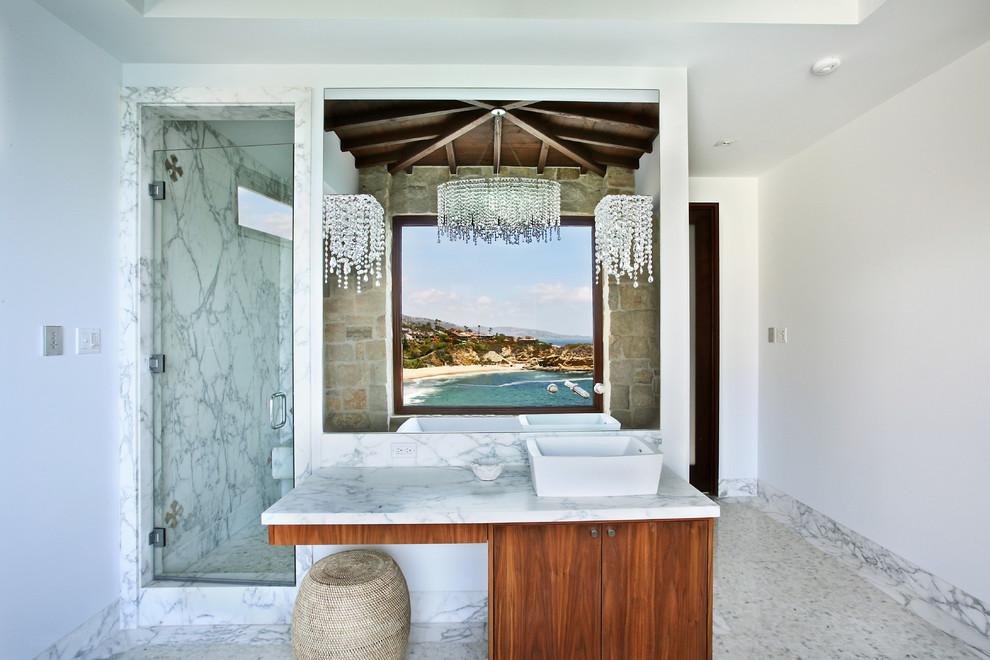 Immagine di una stanza da bagno mediterranea con lavabo a bacinella e lastra di pietra