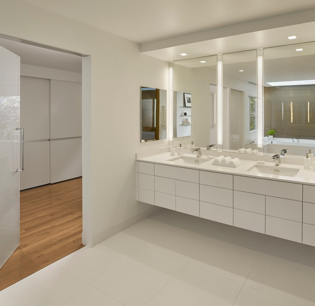 Inspiration for a large contemporary master porcelain floor alcove bathtub remodel in San Francisco with flat-panel cabinets, white cabinets, white walls, an undermount sink, solid surface countertops and white countertops