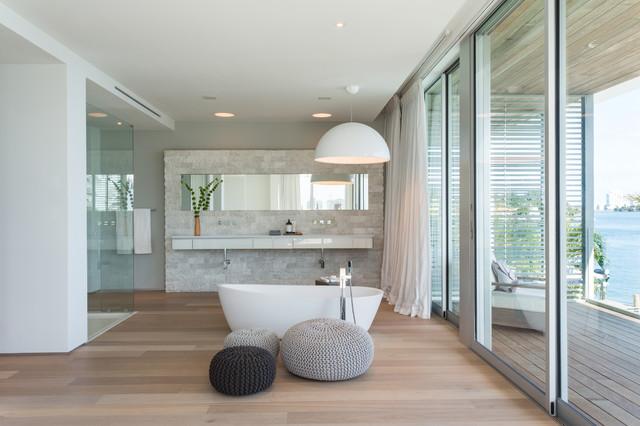 Réalisation d'une grande salle de bain principale design avec un placard à porte plane, des portes de placard blanches, une baignoire indépendante, un sol en bois clair, un mur blanc et un sol marron.