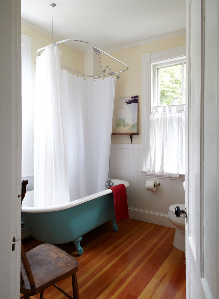 Beach style claw-foot bathtub photo in San Francisco with yellow walls