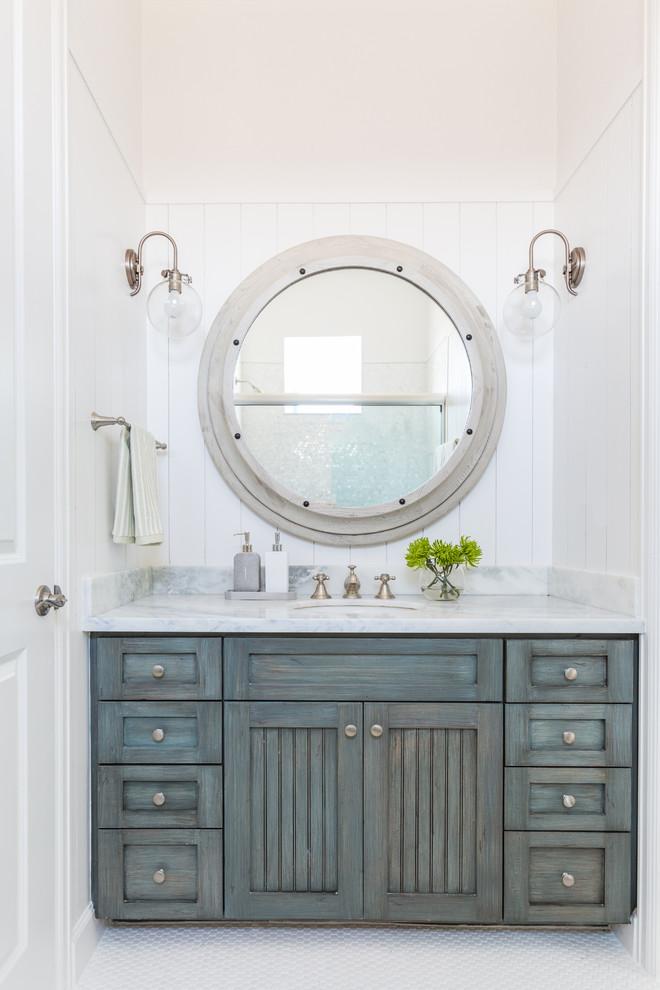 Beach style mosaic tile floor bathroom photo in Houston with blue cabinets