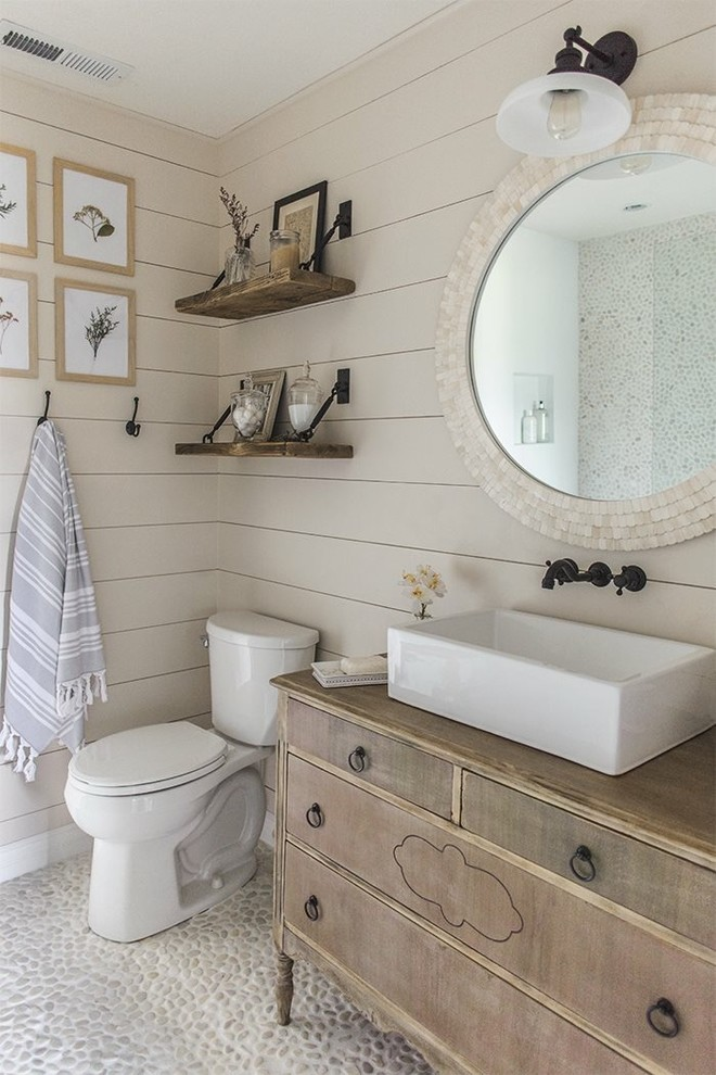 Example of a small beach style 3/4 pebble tile floor and gray floor bathroom design in Phoenix with furniture-like cabinets, distressed cabinets, a two-piece toilet, beige walls, a vessel sink, wood countertops and brown countertops