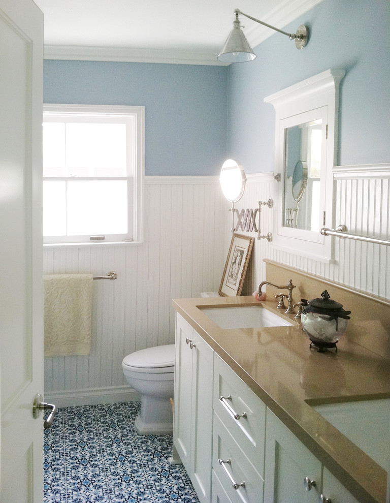 Bathroom - mid-sized coastal blue tile blue floor and ceramic tile bathroom idea in Austin with an undermount sink, shaker cabinets, white cabinets, a one-piece toilet, blue walls, quartz countertops and brown countertops