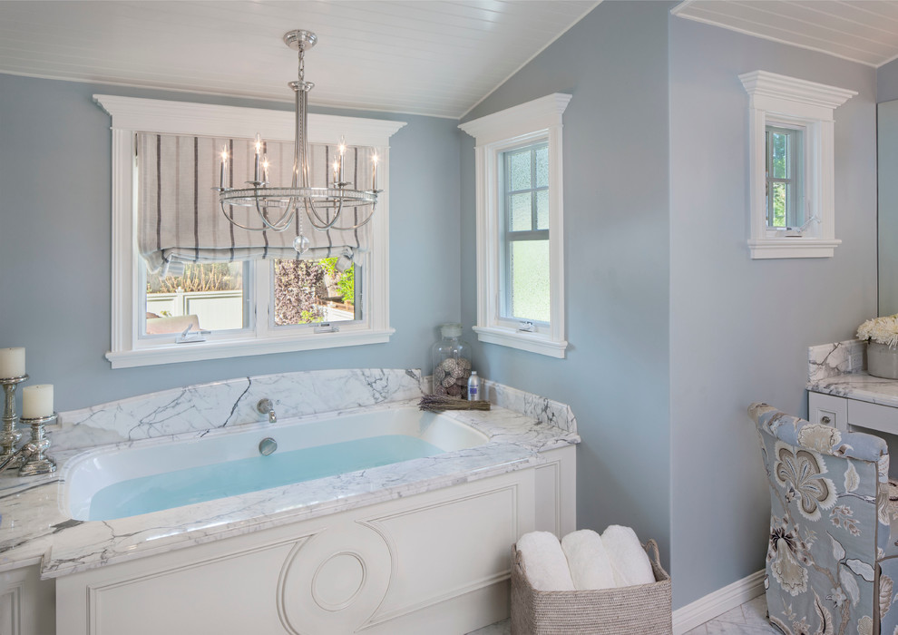 Example of a beach style master white tile bathroom design in Los Angeles with blue walls and an undermount tub