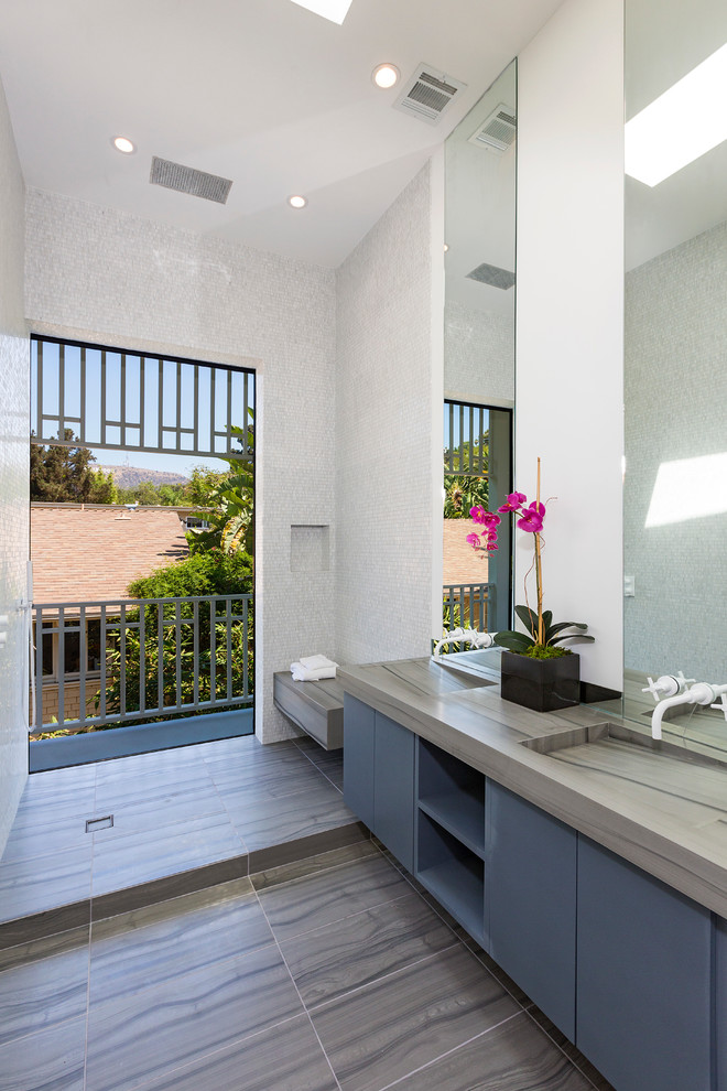 Inspiration for a contemporary white tile and mosaic tile limestone floor bathroom remodel in Los Angeles with an integrated sink, flat-panel cabinets, blue cabinets, white walls and gray countertops