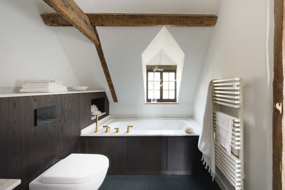 Design ideas for a small contemporary bathroom in Sussex with flat-panel cabinets, brown cabinets, a corner bath, a wall mounted toilet, white walls, black floors and white worktops.