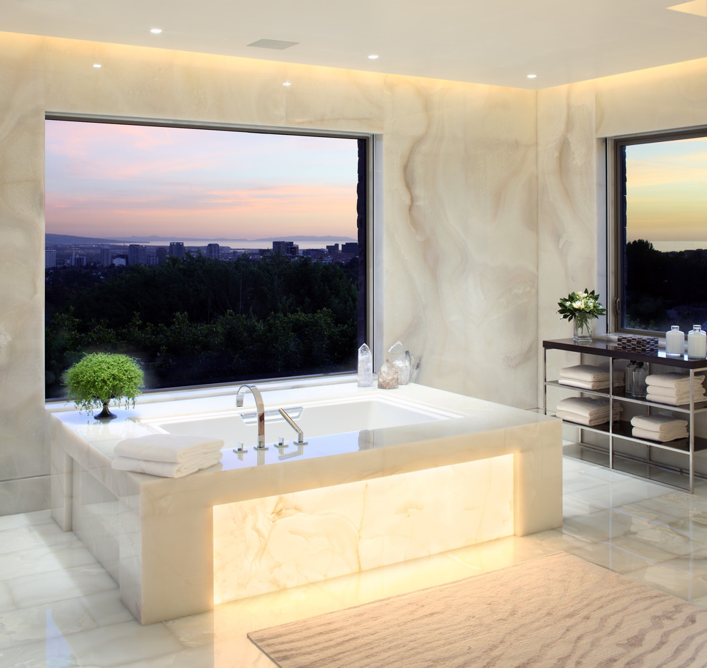 Trendy white tile and stone slab bathroom photo in Los Angeles with an undermount tub