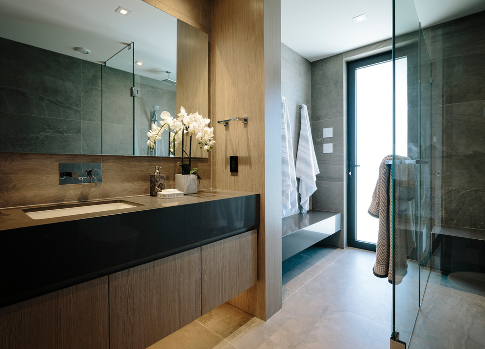 Example of a large trendy gray tile and porcelain tile porcelain floor and gray floor walk-in shower design in Vancouver with flat-panel cabinets, medium tone wood cabinets, gray walls, an undermount sink, quartz countertops, a hinged shower door and gray countertops