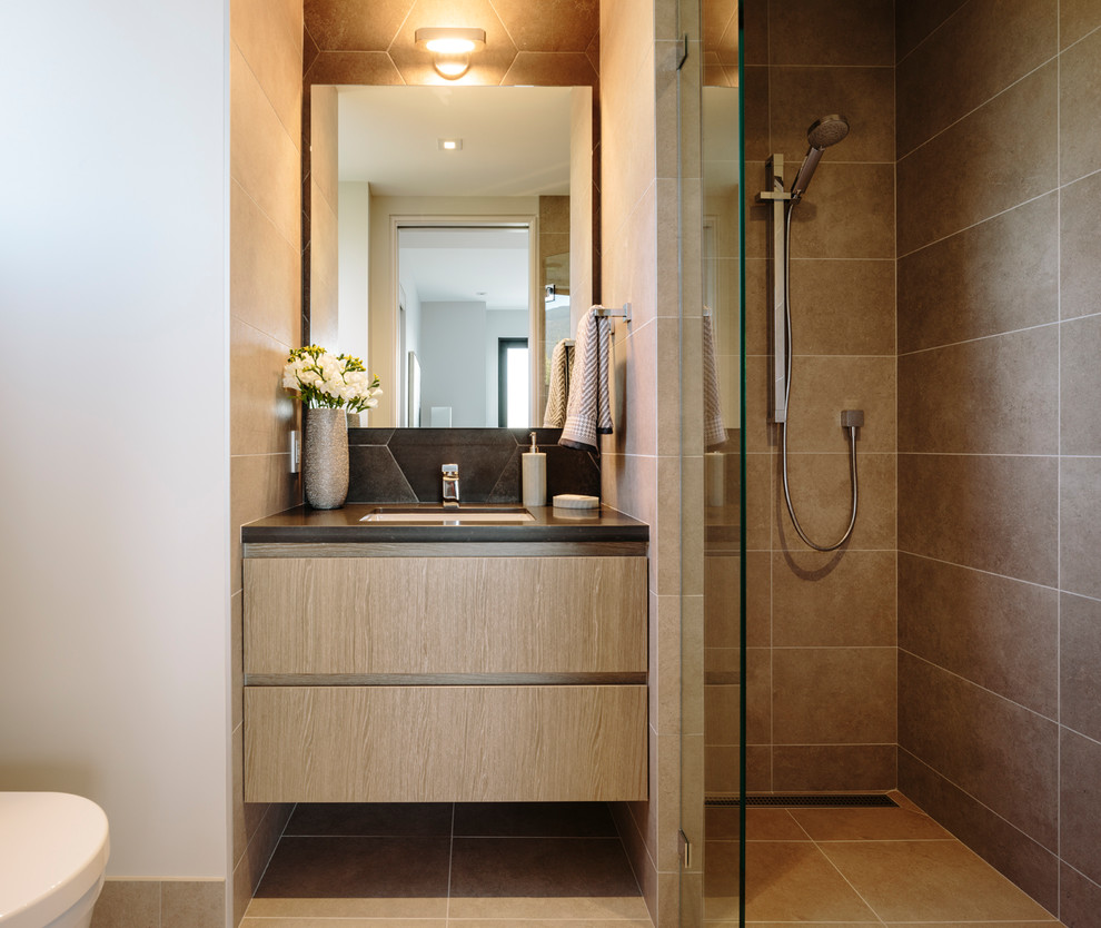 Example of a large trendy kids' porcelain tile and brown tile porcelain floor and brown floor walk-in shower design in Vancouver with flat-panel cabinets, medium tone wood cabinets, a wall-mount toilet, quartz countertops, a hinged shower door, gray countertops, white walls and an undermount sink