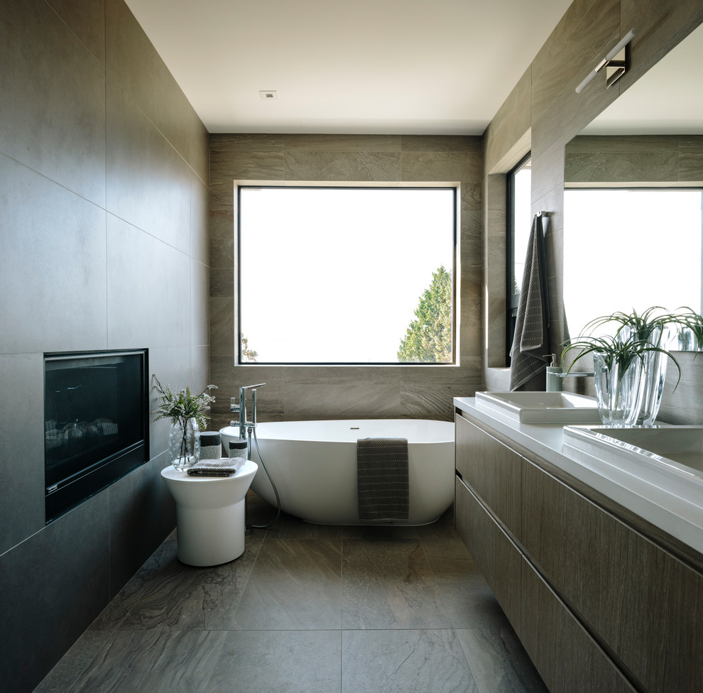 Large trendy master gray tile and porcelain tile porcelain floor and gray floor freestanding bathtub photo in Vancouver with flat-panel cabinets, quartz countertops, white countertops, dark wood cabinets and a drop-in sink