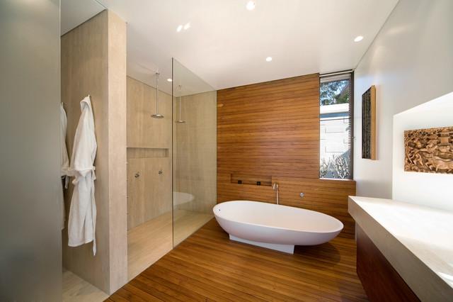 Esempio di una stanza da bagno padronale minimalista con ante lisce, ante in legno scuro, vasca freestanding, piastrelle beige, pavimento in legno massello medio, doccia aperta e doccia doppia
