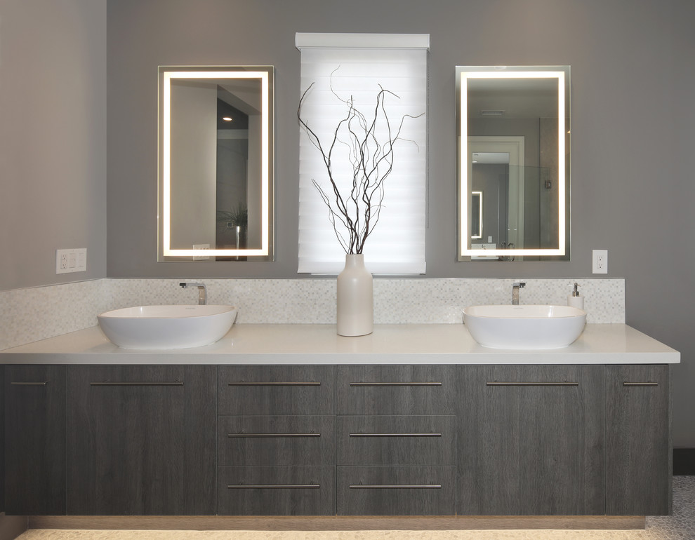 Inspiration for a mid-sized modern master gray tile and stone slab pebble tile floor bathroom remodel with flat-panel cabinets, dark wood cabinets, gray walls, a vessel sink, quartz countertops, a hinged shower door and white countertops