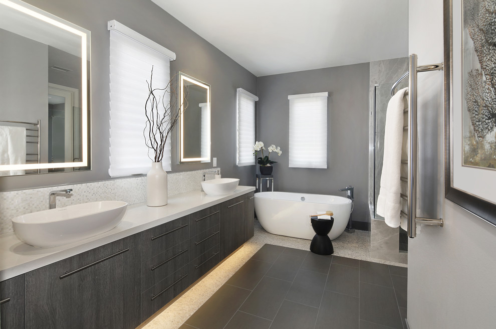Bathroom - mid-sized modern master gray tile and stone slab porcelain tile and gray floor bathroom idea with flat-panel cabinets, dark wood cabinets, gray walls, a vessel sink, quartz countertops, a hinged shower door and white countertops