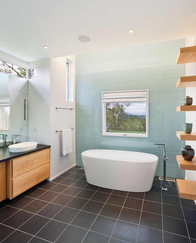 Trendy glass tile freestanding bathtub photo in New York with a vessel sink