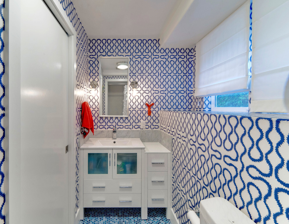 Example of a small transitional kids' blue tile and porcelain tile ceramic floor alcove shower design in San Francisco with an integrated sink, glass-front cabinets, white cabinets, solid surface countertops, a one-piece toilet and blue walls