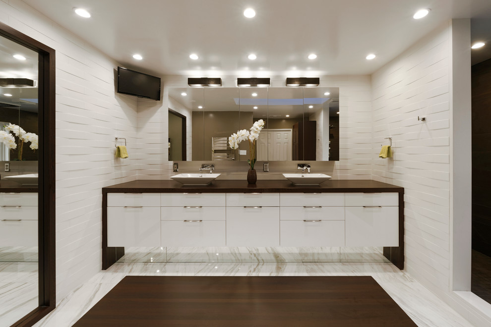 Large trendy master white tile and stone tile marble floor bathroom photo in DC Metro with a vessel sink, flat-panel cabinets, white cabinets, white walls, a one-piece toilet, wood countertops and brown countertops