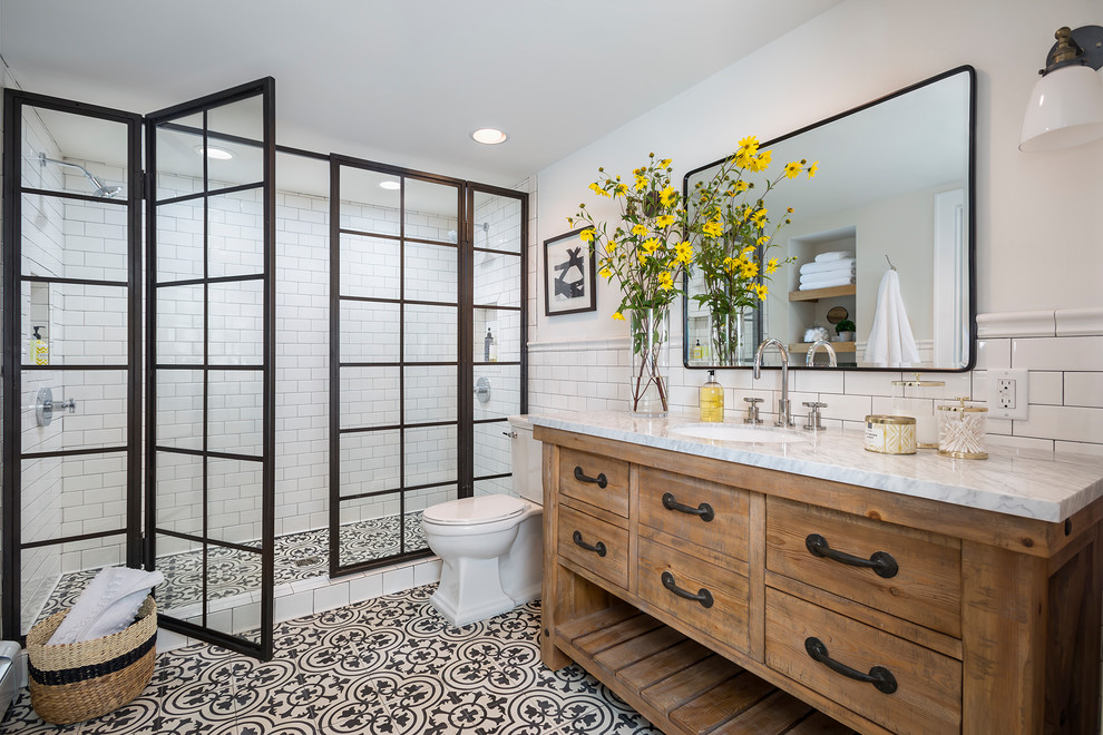 Double shower - large traditional master white tile and subway tile ceramic tile and multicolored floor double shower idea in Los Angeles with furniture-like cabinets, medium tone wood cabinets, white walls, an undermount sink, a hinged shower door, a two-piece toilet and marble countertops