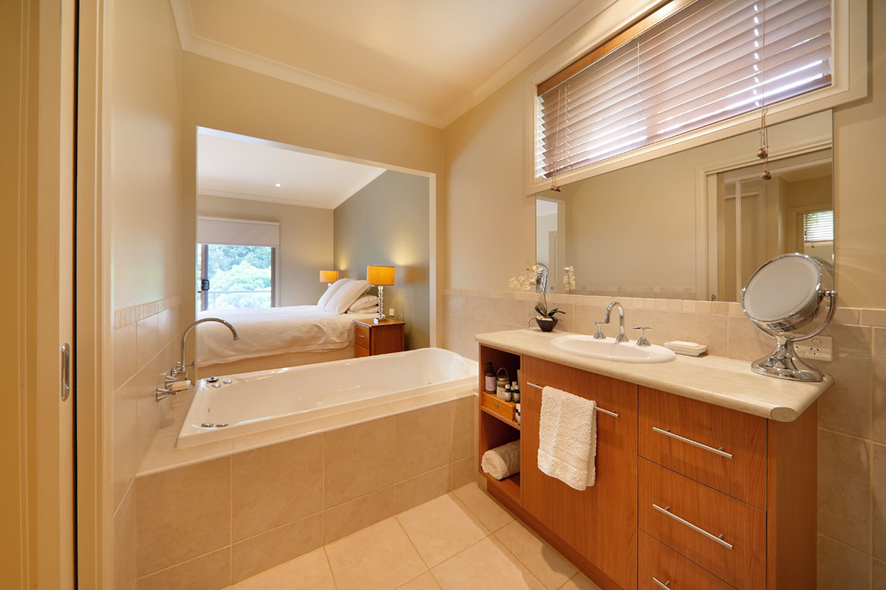 Inspiration for a contemporary beige tile drop-in bathtub remodel in Sydney with a drop-in sink, flat-panel cabinets and medium tone wood cabinets
