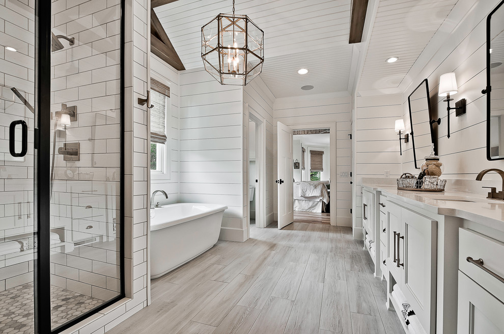 Example of a large arts and crafts master white tile and porcelain tile ceramic tile and beige floor bathroom design in Little Rock with raised-panel cabinets, white cabinets, a two-piece toilet, white walls, an undermount sink, quartz countertops, a hinged shower door and white countertops