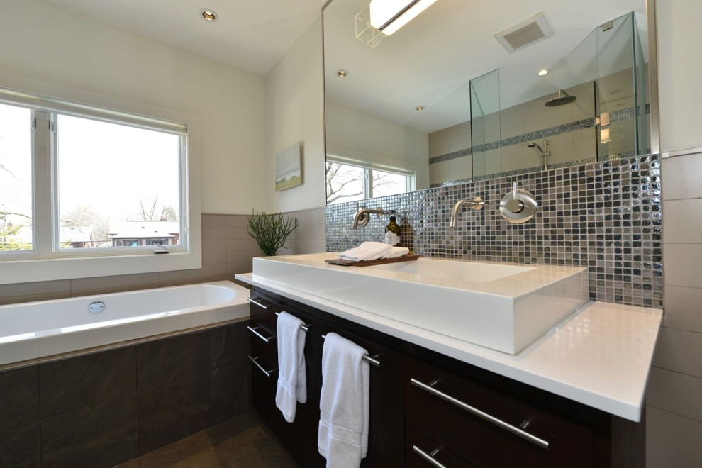 Inspiration for a large contemporary white tile and porcelain tile porcelain floor and brown floor bathroom remodel in Toronto with furniture-like cabinets, brown cabinets, a one-piece toilet, white walls, a vessel sink, solid surface countertops, a hinged shower door and white countertops