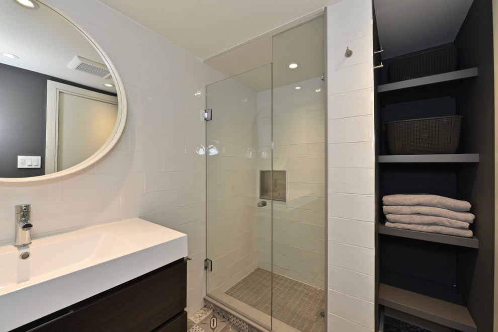 Alcove shower - small modern 3/4 white tile and ceramic tile porcelain floor and gray floor alcove shower idea in Toronto with flat-panel cabinets, brown cabinets, a one-piece toilet, gray walls, an integrated sink, solid surface countertops, a hinged shower door and white countertops