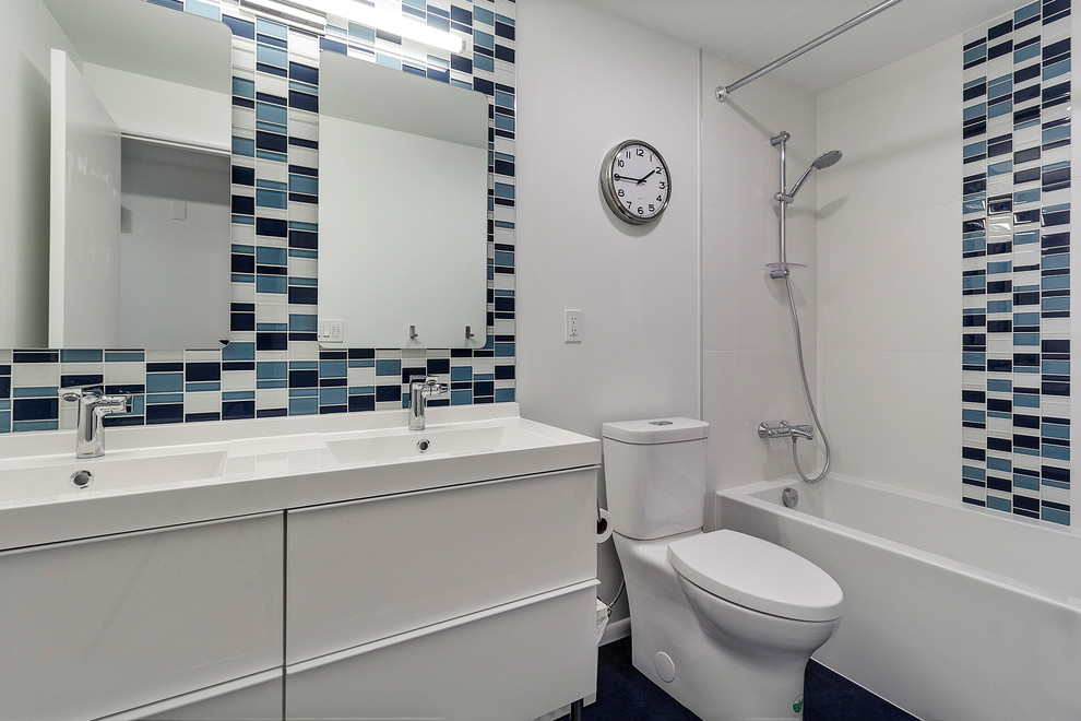 Small minimalist kids' blue tile and mosaic tile linoleum floor and blue floor bathroom photo in Portland with flat-panel cabinets, white cabinets, white walls, an integrated sink, white countertops, a two-piece toilet and quartz countertops