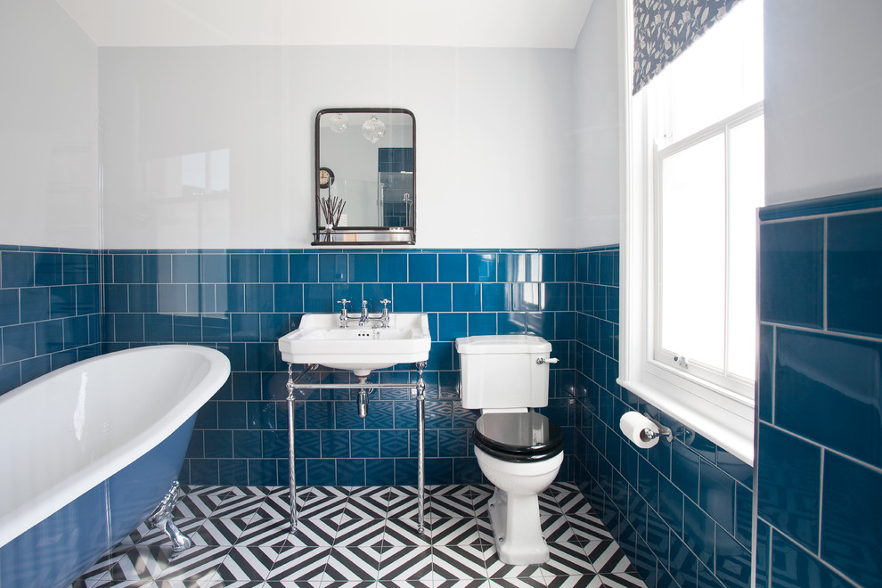 Inspiration for a small timeless blue tile and ceramic tile ceramic tile and multicolored floor corner shower remodel in Sussex with a one-piece toilet, white walls, a pedestal sink and a hinged shower door