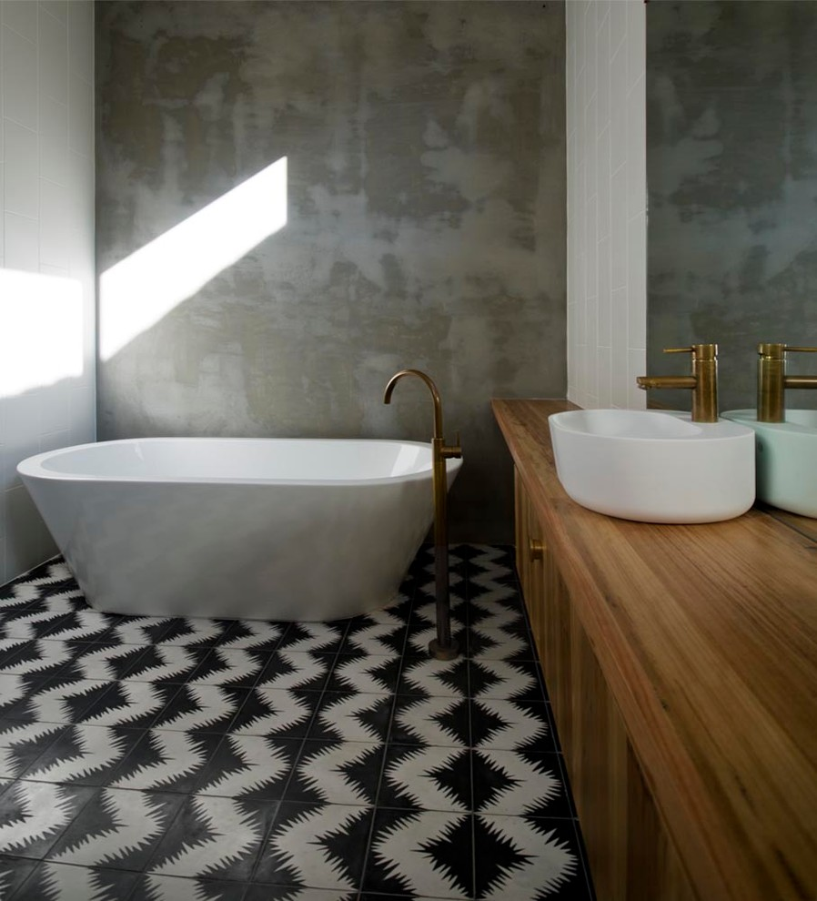 Freestanding bathtub - mid-sized contemporary master cement tile ceramic tile freestanding bathtub idea in Melbourne with a vessel sink, flat-panel cabinets, medium tone wood cabinets, wood countertops, gray walls and brown countertops