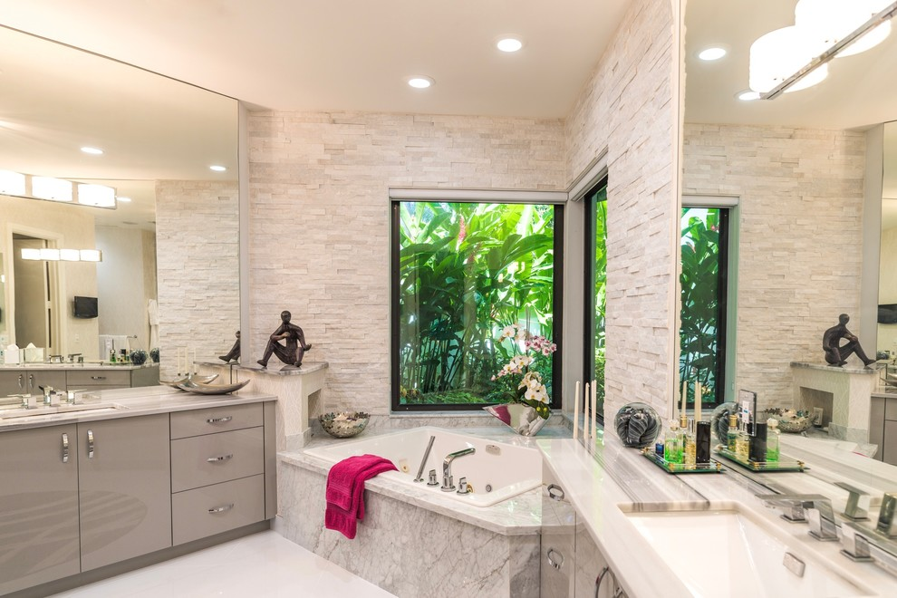 Large trendy master white tile and stone slab ceramic tile bathroom photo in Miami with flat-panel cabinets, gray cabinets, a one-piece toilet, gray walls, an undermount sink and marble countertops