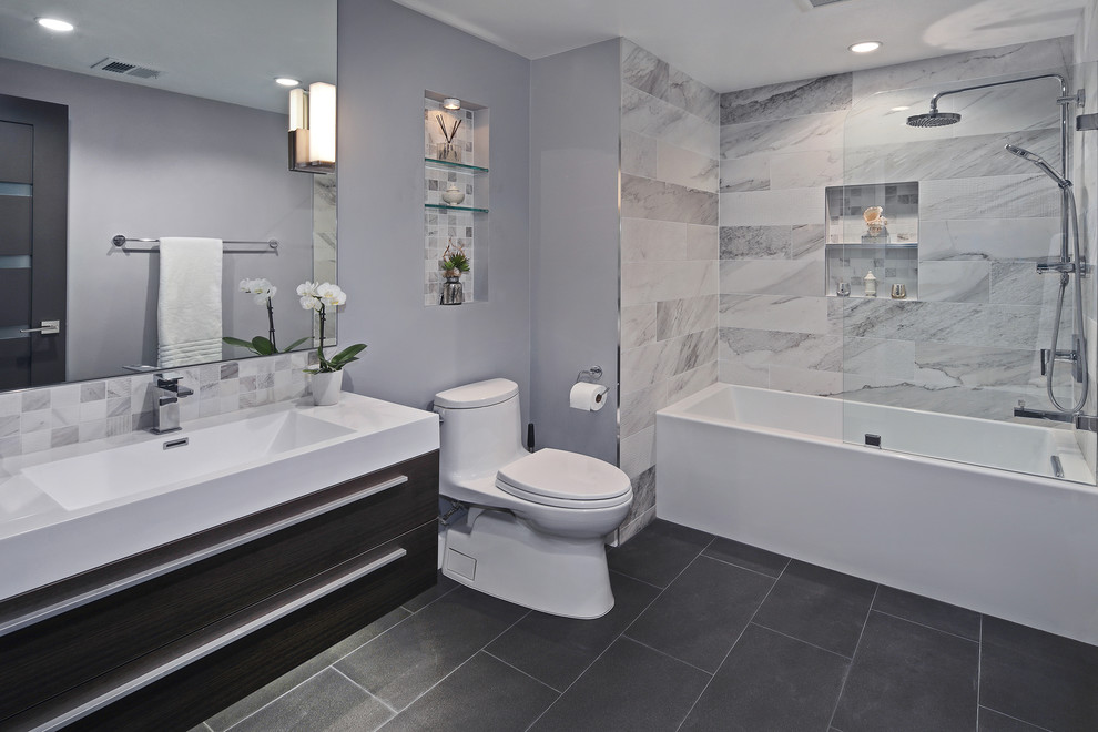 Small trendy gray tile and porcelain tile porcelain tile and black floor bathroom photo in Orange County with flat-panel cabinets, dark wood cabinets, gray walls, an integrated sink, a two-piece toilet, a hinged shower door and quartz countertops