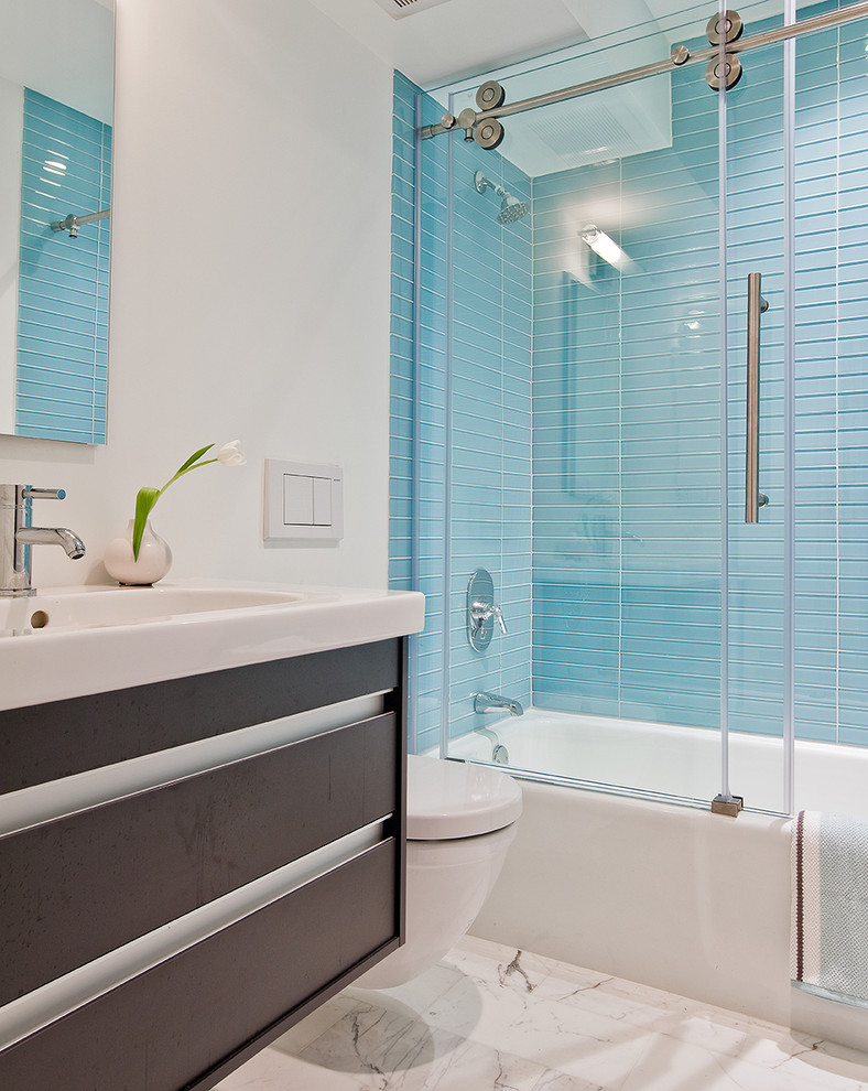 Inspiration for a mid-sized contemporary master blue tile and glass tile marble floor bathroom remodel in Boston with a wall-mount toilet, flat-panel cabinets, dark wood cabinets, white walls, an integrated sink and quartz countertops