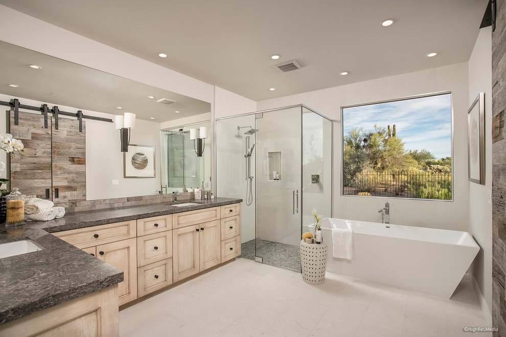 Mid-sized trendy master white tile and porcelain tile porcelain tile freestanding bathtub photo in Phoenix with light wood cabinets, white walls, an undermount sink and marble countertops