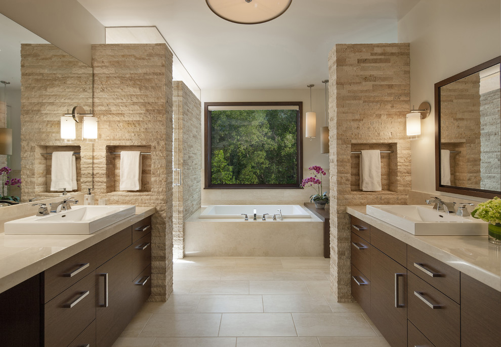 Example of a trendy master beige tile and travertine tile travertine floor drop-in bathtub design in Denver with a vessel sink, flat-panel cabinets, dark wood cabinets, marble countertops and beige walls