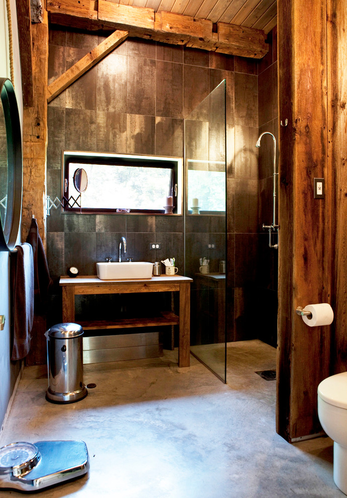 Inspiration for a mid-sized rustic porcelain tile concrete floor and brown floor alcove shower remodel in New York with a vessel sink, open cabinets, medium tone wood cabinets, brown walls and a hinged shower door