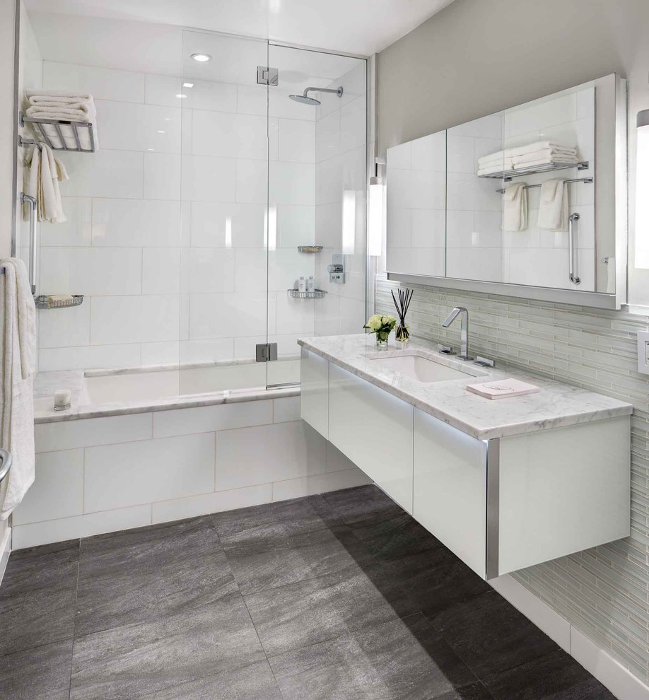 Inspiration for a contemporary white tile gray floor tub/shower combo remodel in New York with an undermount sink, flat-panel cabinets, white cabinets, an undermount tub and gray walls