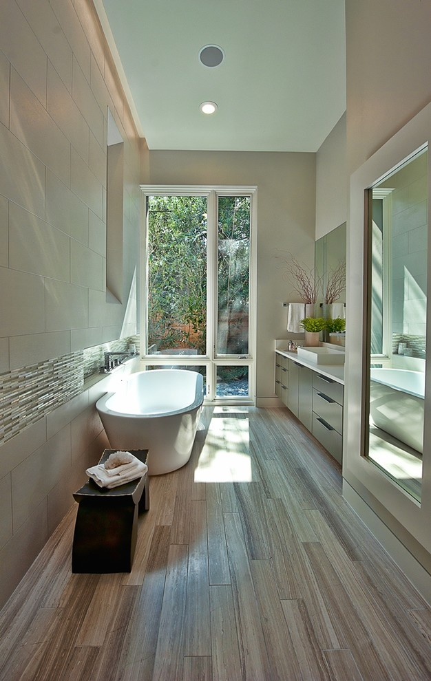 Trendy beige tile and stone tile freestanding bathtub photo in Austin with a vessel sink