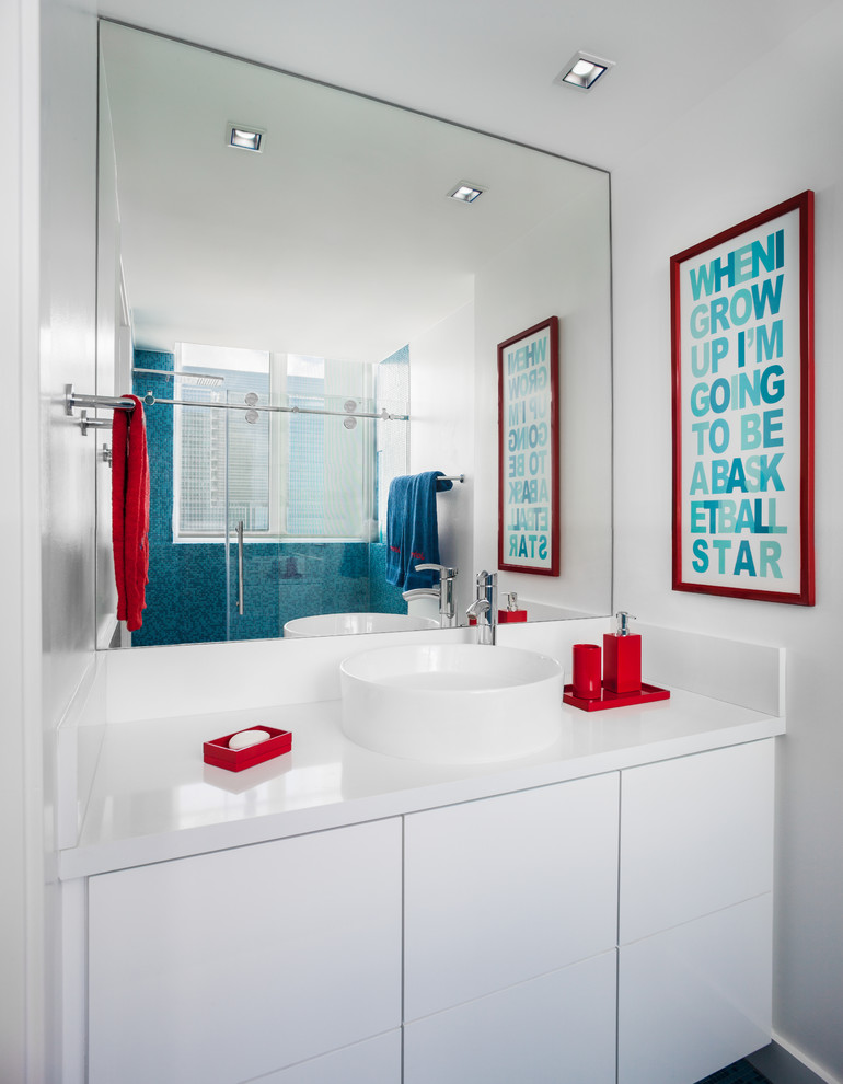 Mid-sized minimalist kids' corner shower photo in Miami with flat-panel cabinets, white cabinets, a one-piece toilet, white walls, a vessel sink and solid surface countertops