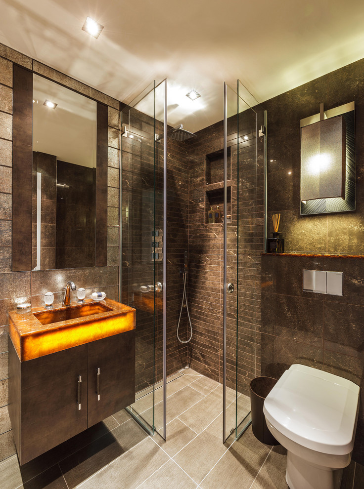 Example of a trendy brown tile corner shower design in London with an integrated sink, flat-panel cabinets and a one-piece toilet