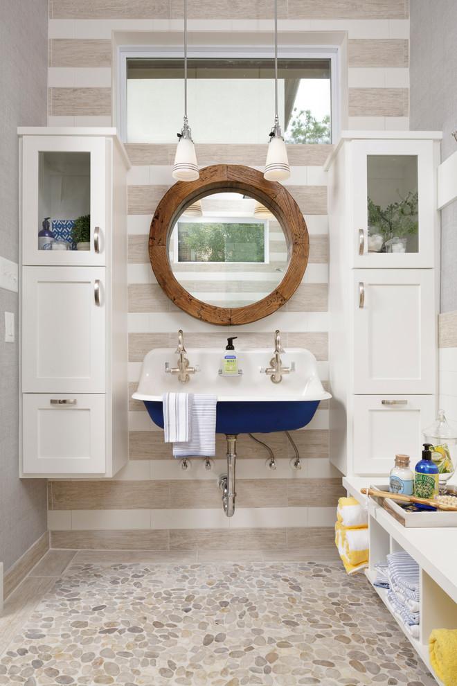 Esempio di una stanza da bagno con doccia al mare di medie dimensioni con lavabo sospeso, ante in stile shaker, ante bianche, pavimento con piastrelle di ciottoli, piastrelle beige, pareti grigie, pavimento beige e top bianco