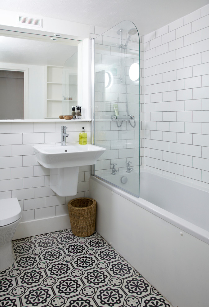 Photo of a small traditional bathroom in London with a wall-mounted sink, a shower/bath combination, a one-piece toilet, white tiles, metro tiles, white walls and an alcove bath.