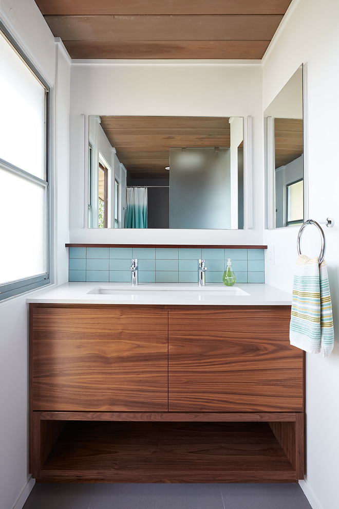 Example of a 1960s blue tile gray floor bathroom design in San Francisco with flat-panel cabinets, medium tone wood cabinets, white walls, an undermount sink and white countertops