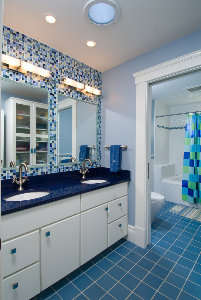 Inspiration for a mid-sized timeless kids' blue tile and mosaic tile ceramic floor and blue floor bathroom remodel in Detroit with white cabinets, flat-panel cabinets, a two-piece toilet, blue walls, an undermount sink, solid surface countertops and blue countertops