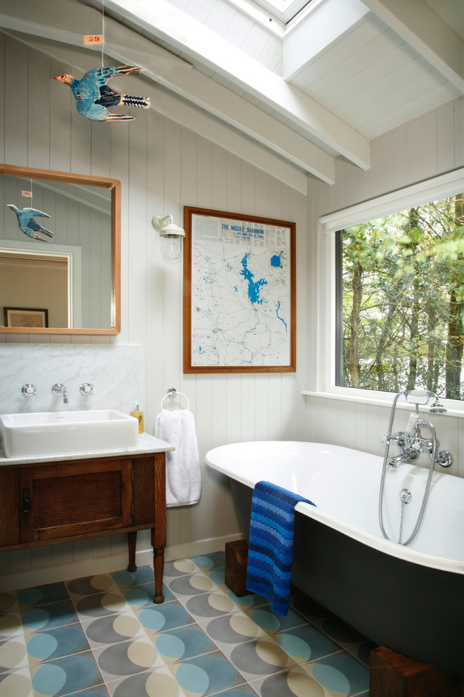 Example of a classic beige tile, blue tile and gray tile freestanding bathtub design in London with furniture-like cabinets, white walls and a vessel sink