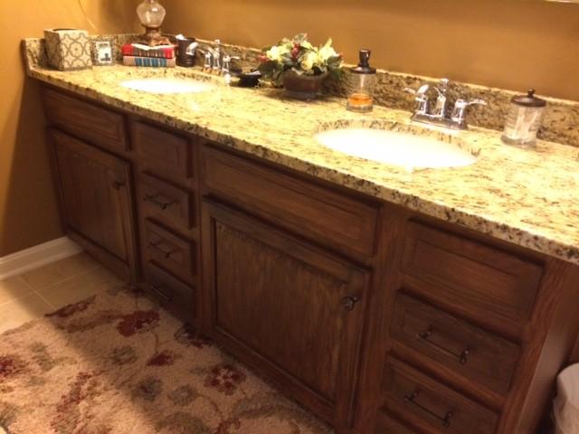 Elegant porcelain tile and beige floor bathroom photo in Cincinnati with raised-panel cabinets, dark wood cabinets, brown walls, an undermount sink and granite countertops