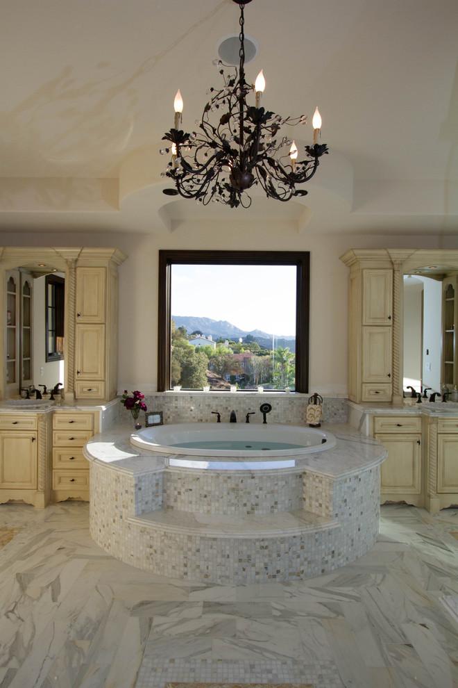 Imagen de cuarto de baño mediterráneo con puertas de armario beige, bañera encastrada, baldosas y/o azulejos blancos y baldosas y/o azulejos de piedra