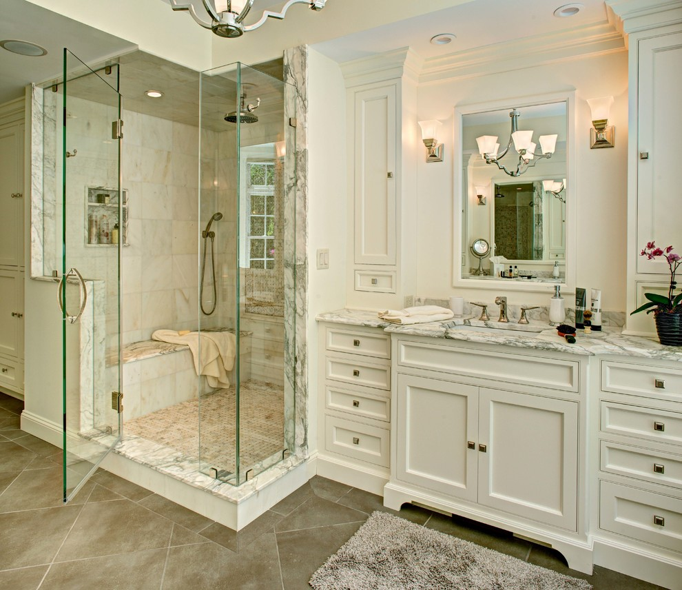 Example of a mid-sized classic master beige tile, white tile and marble tile porcelain tile and beige floor alcove shower design in New York with beaded inset cabinets, white cabinets, white walls, an undermount sink, marble countertops and a hinged shower door